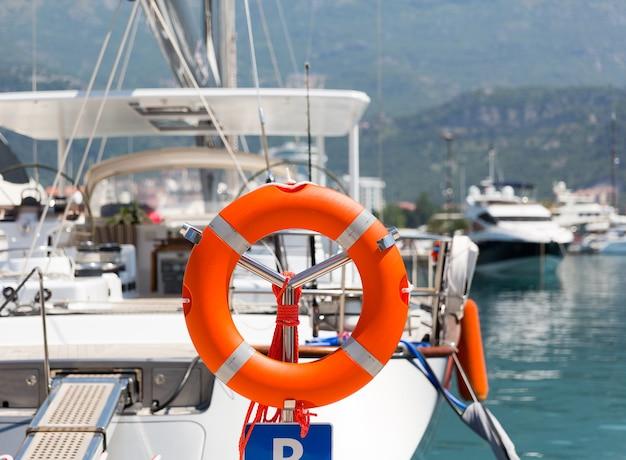 Спасательный круг в морском порту против роскошной яхты
