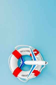 Lifebuoy and model of airplane on blue background. summer or vacation concept. copy space.
