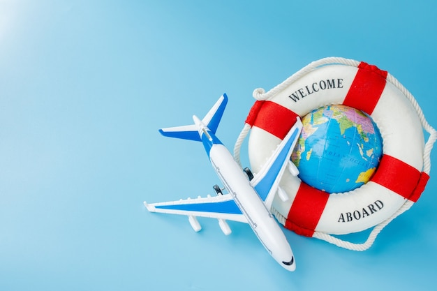 Lifebuoy, model of airplane and globe on blue background. summer or vacation concept. copy space.