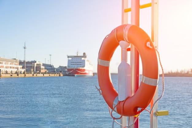 Спасательный круг на пристани в порту, на заднем плане пассажирский лайнер в бухте.