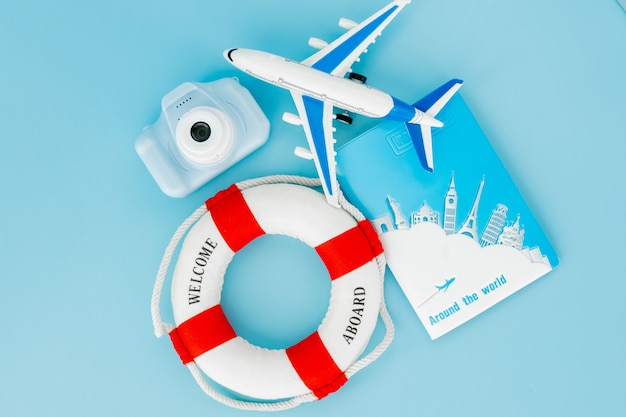 Lifebuoy, 여권, 카메라, 파란색 배경에 비행기 모델. 여름 또는 휴가 개념. 공간을 복사하십시오.