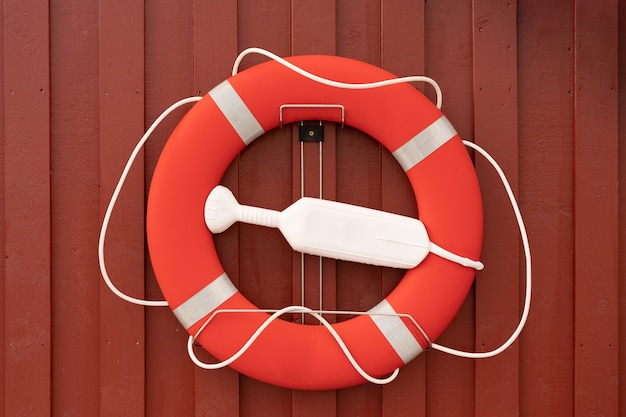 Lifebuoy on red wooden wall