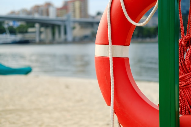 Спасательный круг с веревкой, свисающей с металлического столба на пляже на фоне реки города