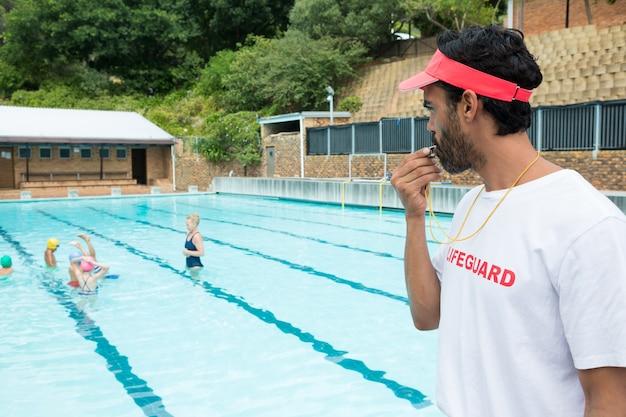 화창한 날에 수영장에서 노는 학생들이 휘파람을 불고있는 인명 구조 원