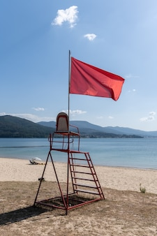 Lifeguard chair with red flag waving. no swimming concept