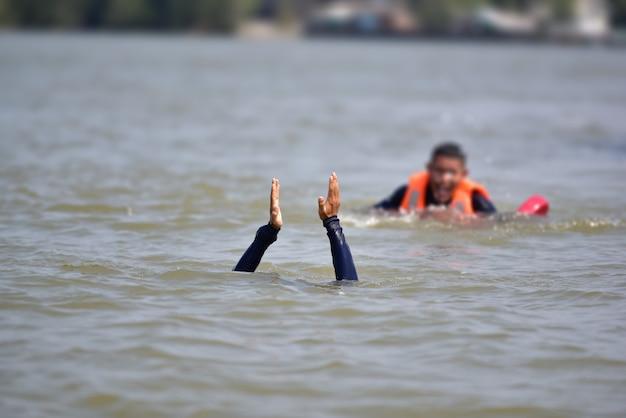 Спасатель помогает жертве утонуть в реке