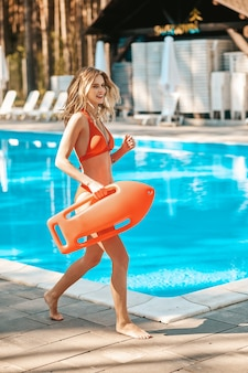 Lifeguard. a long-haired female lifeguard running to the pool
