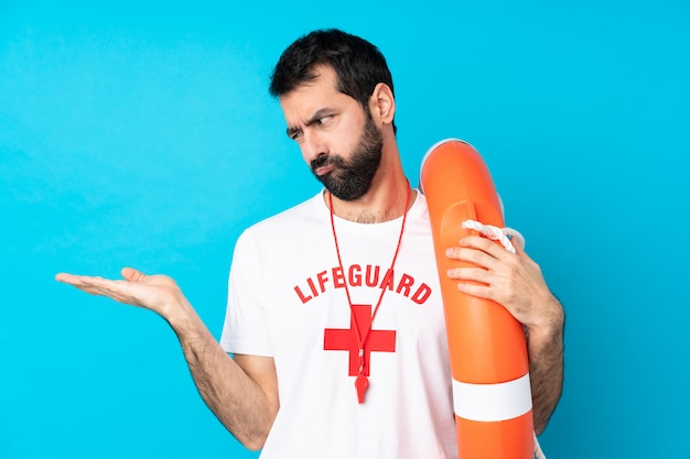 Lifeguard man over blue holding copyspace with doubts