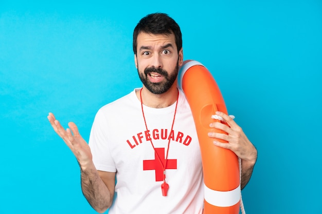 Lifeguard man over blue making doubts gesture