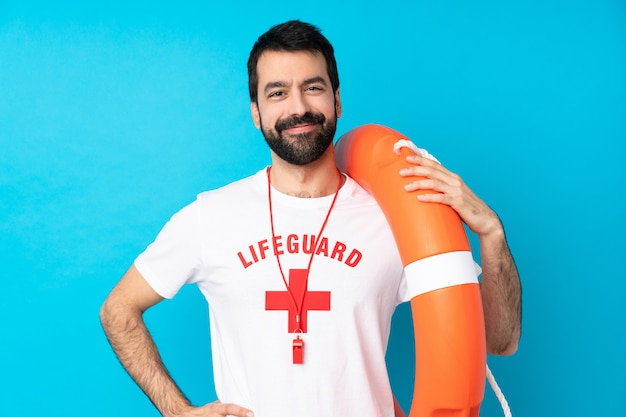 Lifeguard man over blue posing with arms at hip and smiling