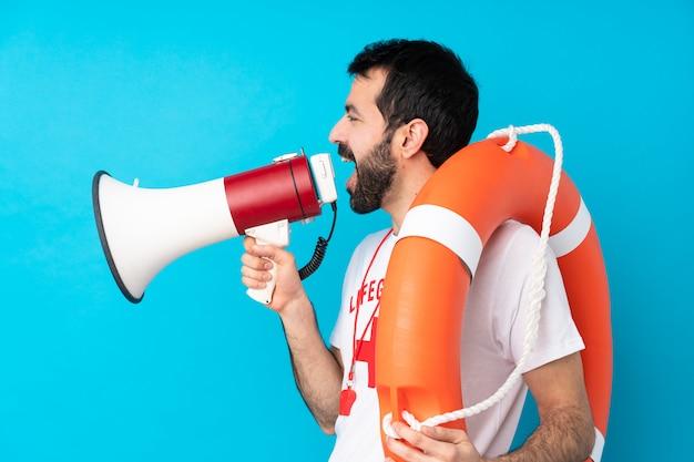 Lifeguard man over blue shouting through a megaphone