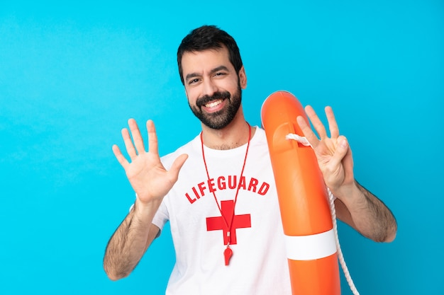 Lifeguard man over blue wall counting eight with fingers