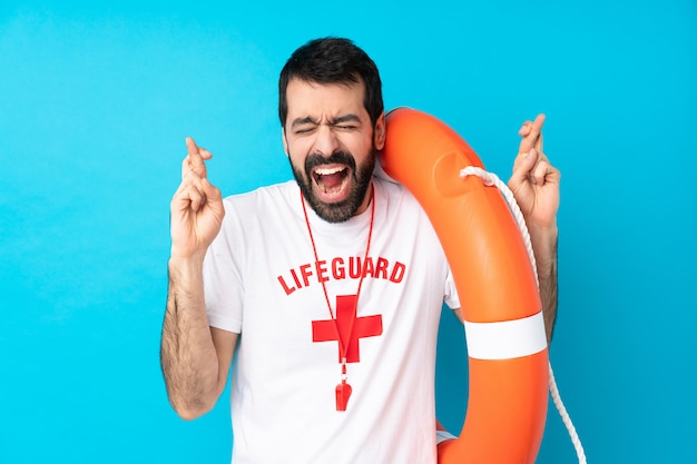 Lifeguard man over blue with fingers crossing