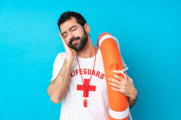 Lifeguard man over isolated blue wall making sleep gesture in dorable expression