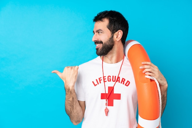 Lifeguard man over isolated blue wall pointing to the side to present a product