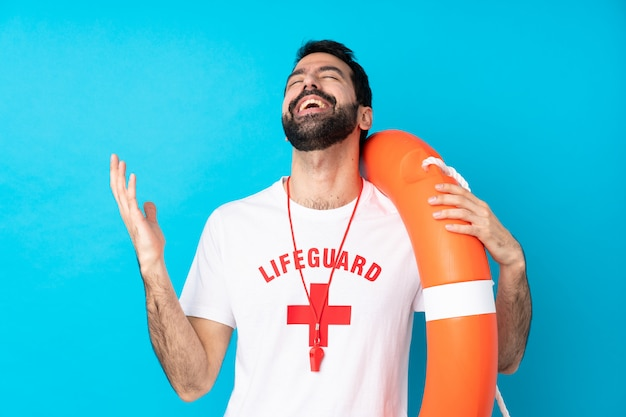 Lifeguard man over isolated blue wall smiling a lot