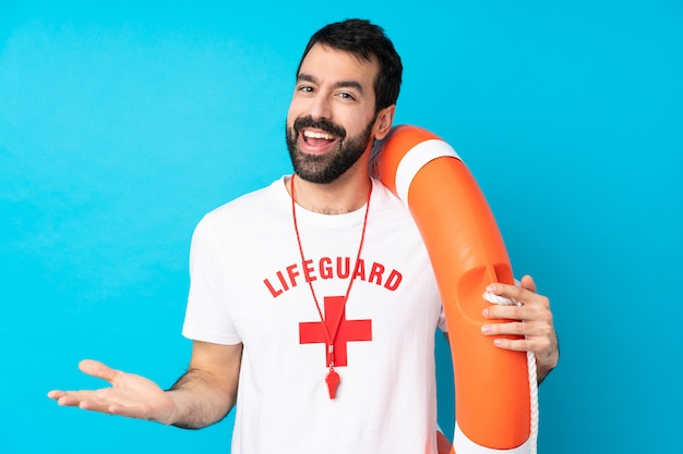Lifeguard man over isolated blue wall smiling