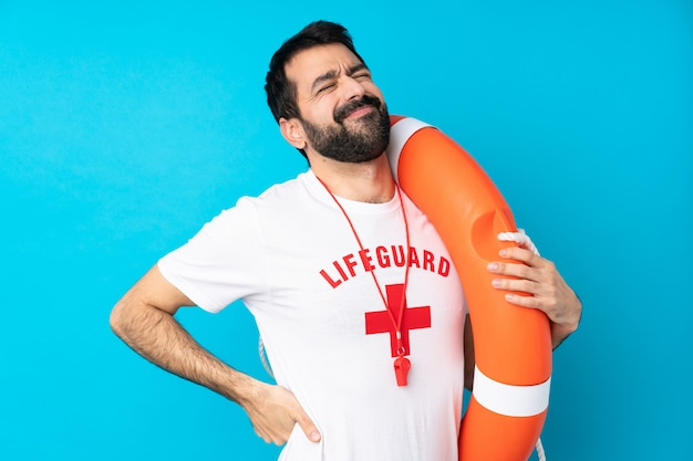 Lifeguard man over isolated blue wall suffering from backache for having made an effort