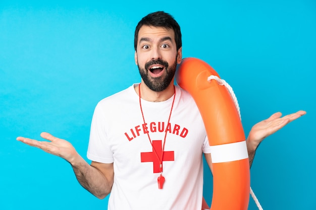 Lifeguard man over isolated blue wall with shocked facial expression