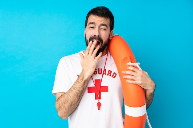 Lifeguard man over isolated blue wall yawning