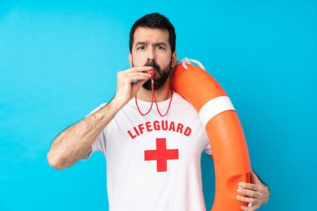 Lifeguard man over isolated blue wall