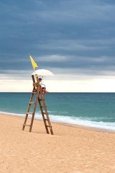 Спасатель на башне на пустынном пляже Premium Фотографии