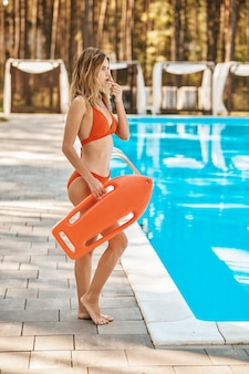 Lifeguard. a pool lifeguard in a red swimming suit warning the visitors