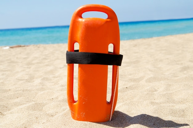 Lifeguard rescue can close up. orange rescue buoyancy stubbed vertical in sand.