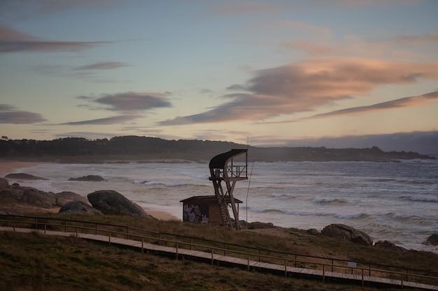 Torre bagnino sulla spiaggia durante il tramonto nel parco naturale di corrubedo in spagna