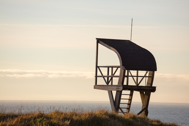 Lifeguard tower in a field surrounded by the sea under a cloudy sky in the evening