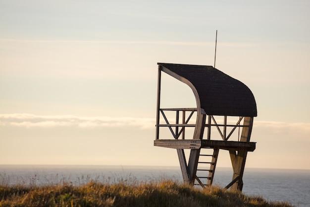 夕方の曇り空の下で海に囲まれたフィールドのライフガードタワー
