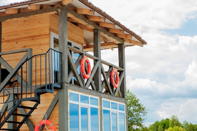 Lifeguard tower for rescue baywatch on beach. wooden house on sea shore on cloudy sky background. summer vacation and resort. public guarding and safety concept