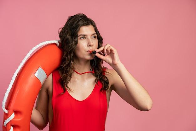 ライフブイを肩に乗せたライフガードが口笛を吹くと、危険を報告します。ピンクの背景に魅力的な女の子