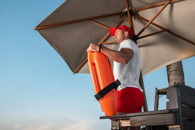 Lifeguard with a rescue orange buoy