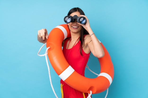 Lifeguard woman over isolated blue wall with lifeguard equipment and with binoculars