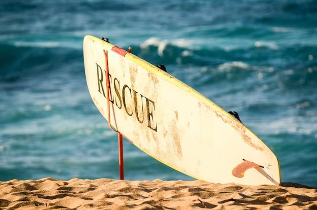 ライフガードの救助サーフボード、サンセットビーチ、オアフ島、ハワイの背景に波があります