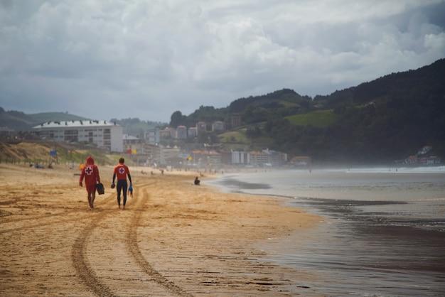 美しい空のビーチを歩いていくライフガード
