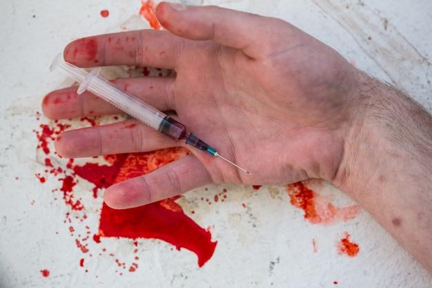 Безжизненная рука с кровавым шприцем