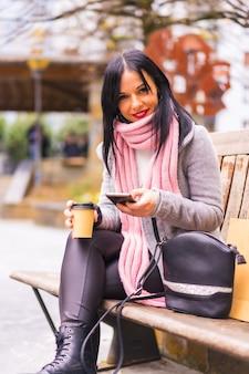 ライフスタイル、紙袋とテイクアウトのコーヒーを持って街で買い物をしている白人のブルネットの女の子、座って電話でメッセージを送信