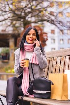 ライフスタイル、紙袋とテイクアウトのコーヒーを持って街で買い物をしている白人のブルネットの女の子、ベンチに座って笑っている