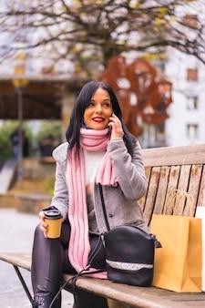 ライフスタイル、紙袋と持ち帰り用のコーヒーを持って街で買い物をしている白人のブルネットの女の子、電話に座って