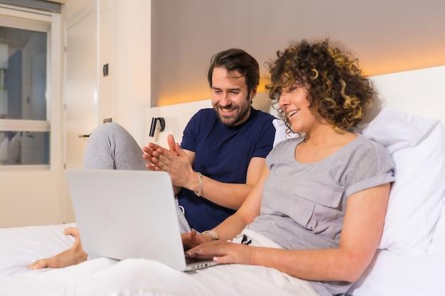 Образ жизни, пара в пижаме на кровати просматривает онлайн-бронирование на компьютере