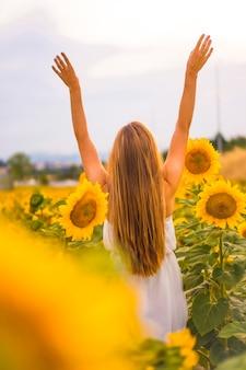 Lifestyle, довольно кавказская блондинка в поле подсолнухов в белом платье, с поднятыми руками