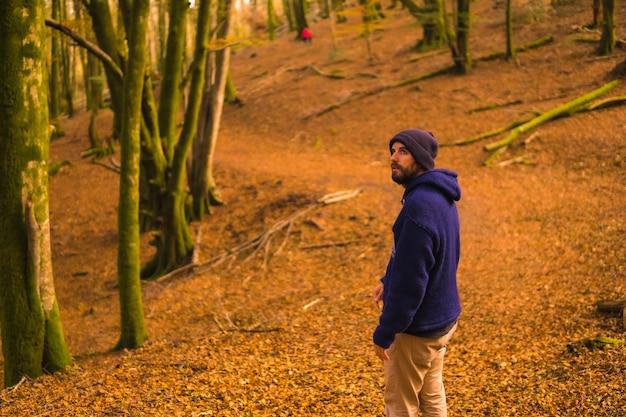ライフスタイル、青いウールのセーターと秋の森を楽しむ帽子の笑顔の若い男。バスク地方、ギプスコア、サンセバスティアンのアルティクツァの森。スペイン