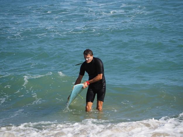 ライフスタイル。疲れたサーファーが水から出てきます。サーフボード付き。