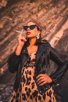 Образ жизни, молодая брюнетка в кожаной куртке и леопардовом платье на закате солнца на побережье в темных очках. молодой человек курит и смотрит чувственно с платком