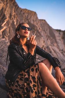 Образ жизни, молодая брюнетка в кожаной куртке и леопардовом платье на закате солнца на побережье в темных очках. молодой человек курит и смотрит с осанкой