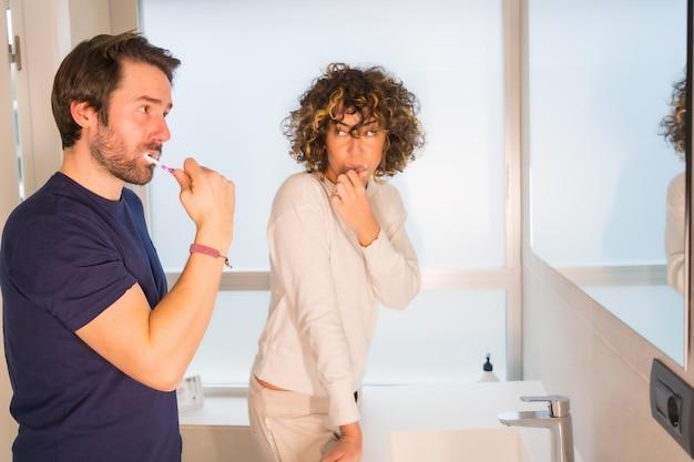 ライフスタイル、パジャマ姿の若い白人カップルがとても幸せに歯を掃除