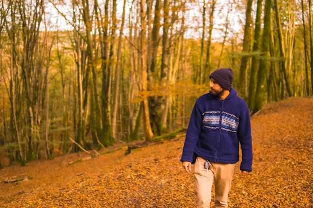 ライフスタイル、秋の森を楽しむ青いウールのセーターを着た若い男。バスク地方、ギプスコア、サンセバスティアンのアルティクツァの森。スペイン