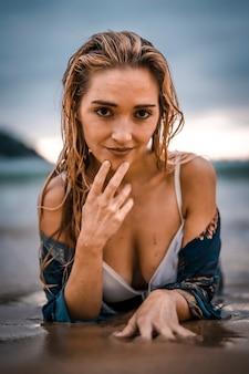 라이프 스타일, 흰색 비키니와 함께 해변에서 매혹적인 표정을 지닌 젊은 여성